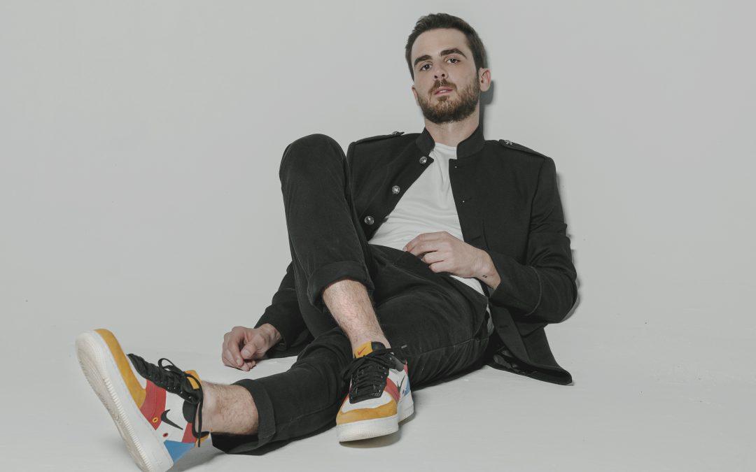 en la imagen se observa a Ivan Zavala sentado en el piso en un fondo blanco, vestido de negro con championes de colores